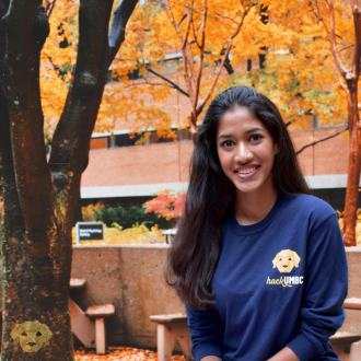 Young woman sits in front of a brick building and tree in the autumn. She wears a long-sleeved t-shirt with a logo for hackUMBC.