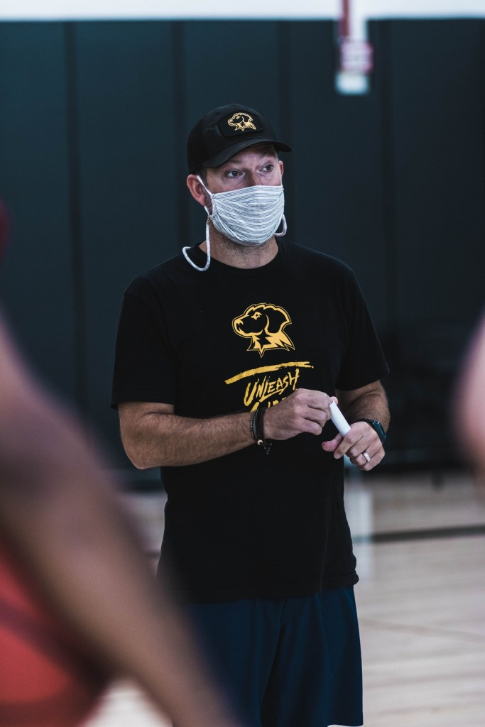 Man stands wearing black and gold Retriever hat and t-shirt, and striped cotton face mask.