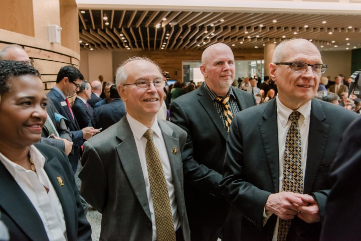 Four administrators in a large hall