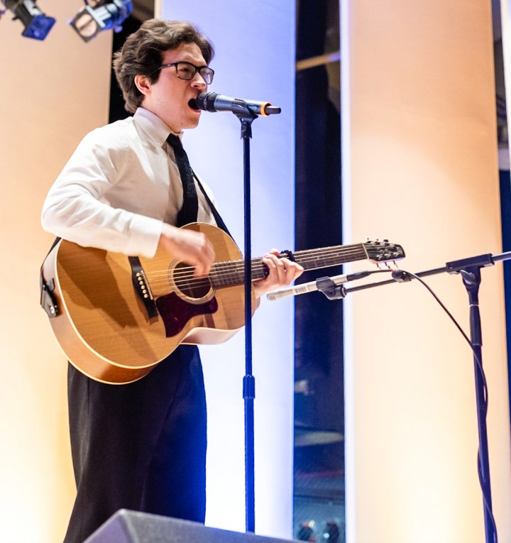 Young man in dress shirt and tie sings into a mic while playing guitar.