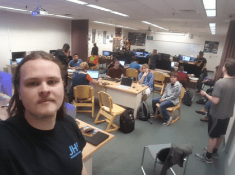 Young white man in black t-shirt looks at the camera, while several other students are seated and standing in the background, around tables and laptops.