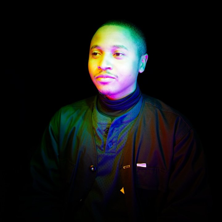 Portrait of a young black man lit by multi-colored neon lights. He wears a buttoned shirt and jacket.