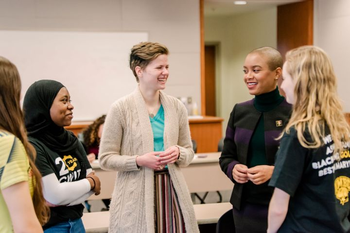 Five women in conversation, smiling. One wears a shirt with UMBC logo. Another's shirt says 20 Years CWIT.