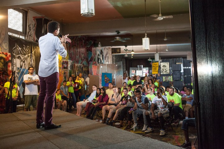 Young man stands on a stage speaking to a crowd of seated young people in a small rooms. Paintings and posters hang on the walls.