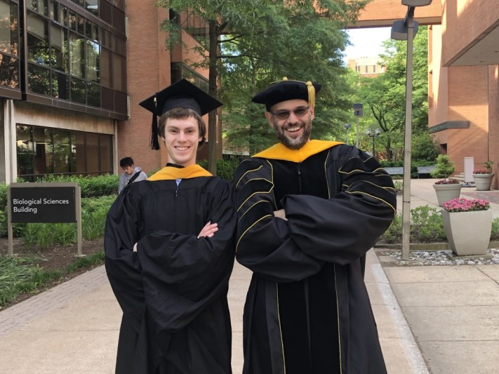 Nathan Myers and Sebastian Deffner in graduation robes, grinning, on UMBC's Academic Row.