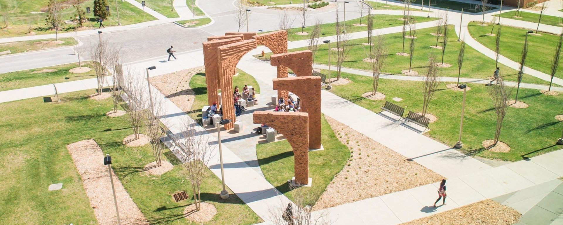 A large outdoor sculpture made of orange colored cement shaped in eight consecutive arches