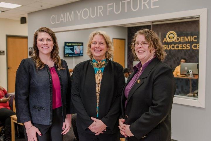 "Three woman in black blazers and dress shirts stand in an office lobby. Behind them a sign reads ""Claim Your Future."""