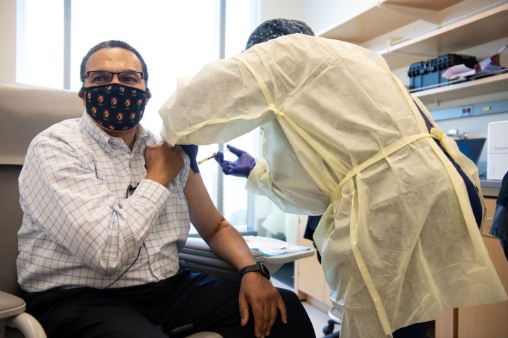 Middle-aged black man with glasses and a face mask receives a shot from a medical professional wearing protective gear. He wears a blue and white dress shirt and dark slacks.