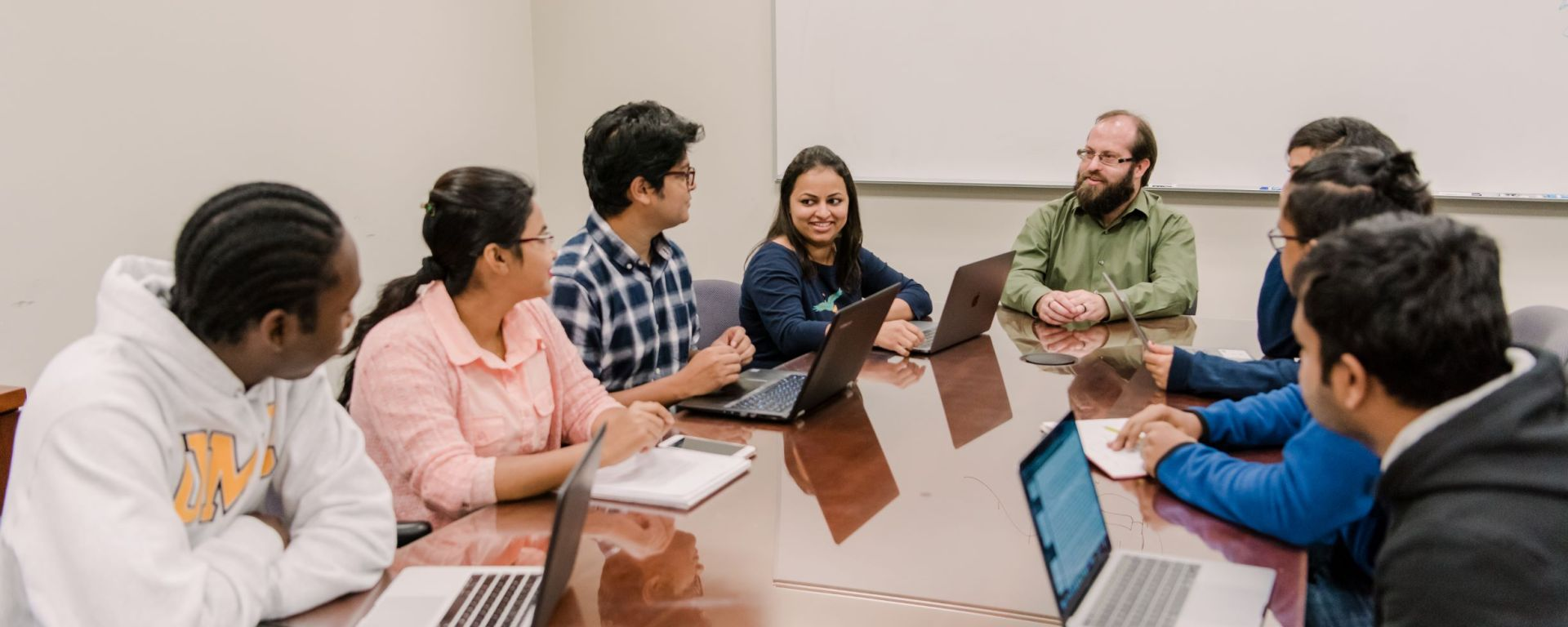 Seven students and a professor sit around a conference table. Five students have open laptops and two are taking notes on paper.