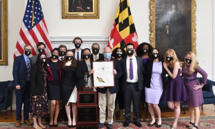 Over a dozen people in business attire, wearing UMBC face masks, stand for a portrait. They hold a framed proclamation. Maryland and US flags stand in the background.