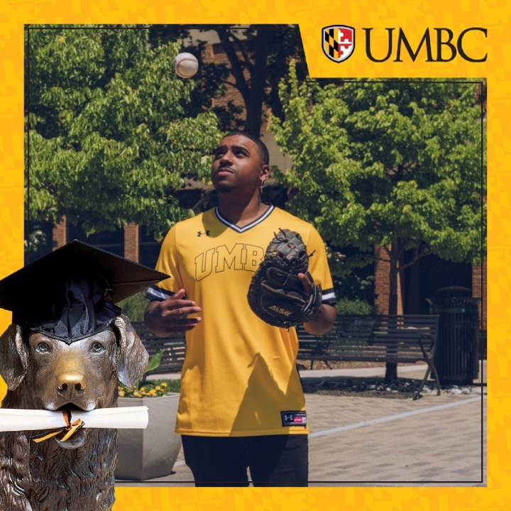 A student wearing a gold UMBC jersey, tosses a baseball. The student is holding a baseball glove.