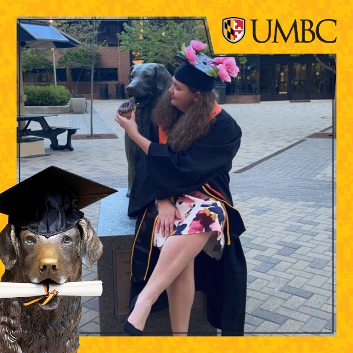 A student wearing a dress and graduating regalia, sits near the True Grit statue, and pretends to feed the statue a donut.