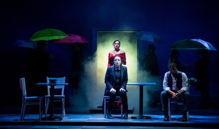 Student actors stand on a darkly lit stage