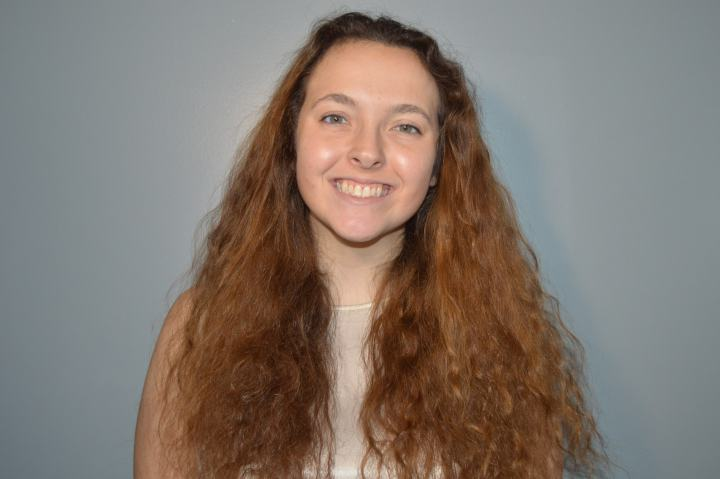 A young woman with long light brown curly hair smiles at the camera.