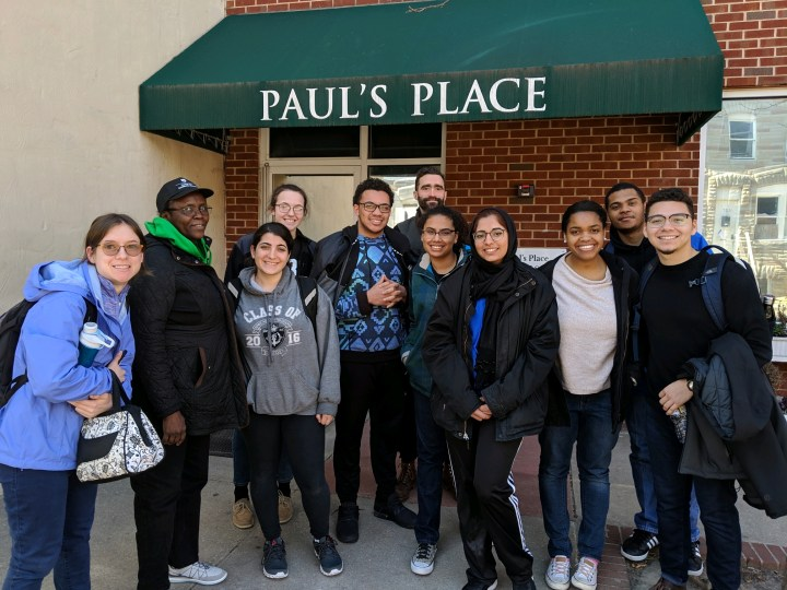 A group of eight young people with three adults wearing winter coats stand before a brick building with a green awning that says Paul's Place in white letters.