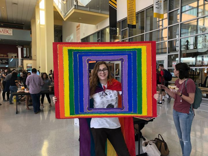 Young person stands inside a photo frame painted with rainbow colors and glitter. They wear a festive, multicolored cape.