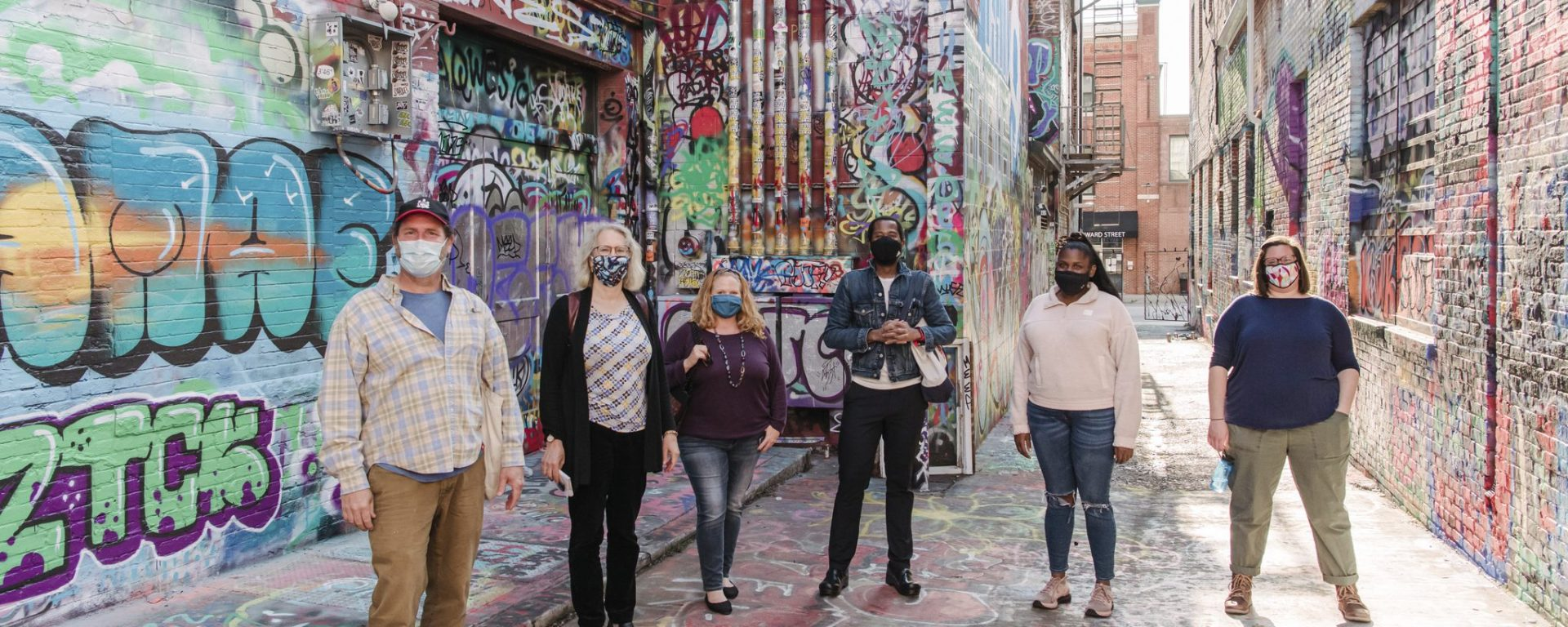 Six people, all wearing masks, standing in a road. The surrounding walls have graffiti on them.