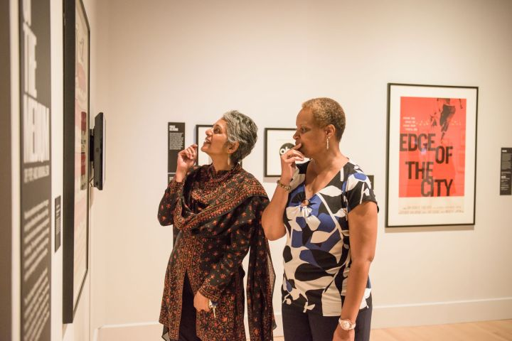Two women look at artwork in a gallery