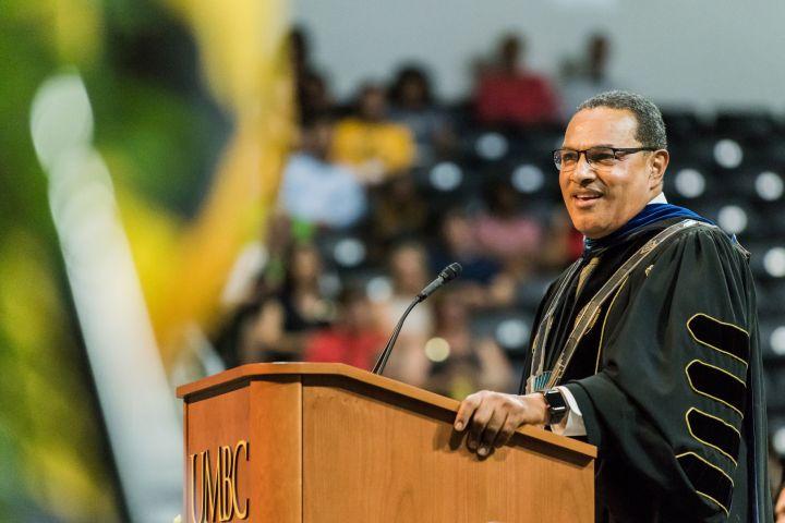 """Man stands at podium in full academic regalia. Podium sign reads """"UMBC."""""""