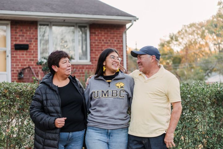 Young woman in UMBC sweatshirt smiles while embracing two older adults, standing in front of a home.