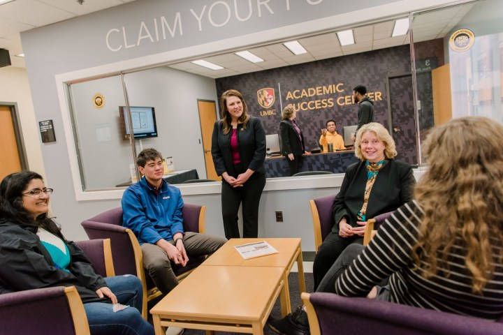 Eight people gather in an office with sign reading UMBC Academic Success Center.