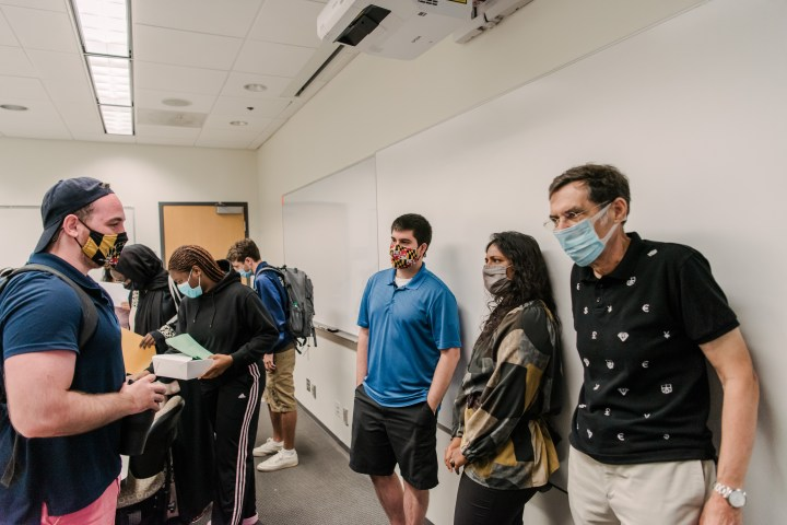 Two people wearing face masks talk to each other with numerous people and a white board in the background.