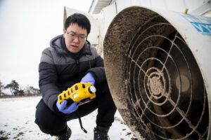 Tian Xia monitors the methane levels coming out of a pig holding pen before setting up a lab-scale non-thermal plasma device at the Barton Farms family pig farm in Homer, MI. Image credit: Robert Coelius/Michigan Engineering