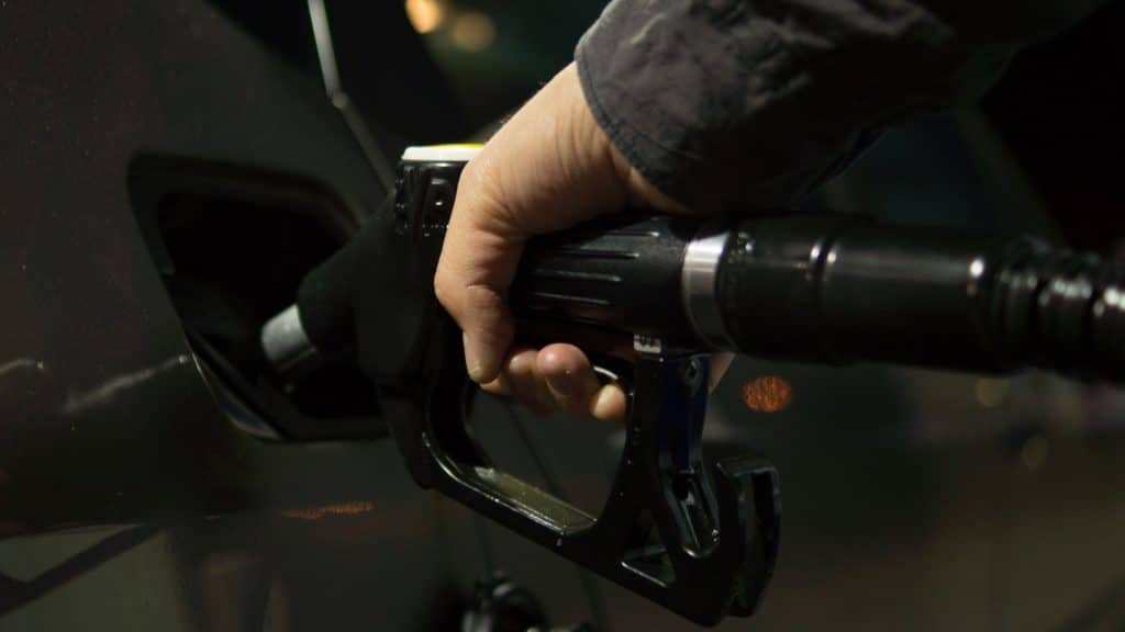A person refills a car's gasoline tank.