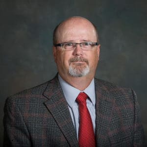 man wearing glasses, a red tie and a checked blazer