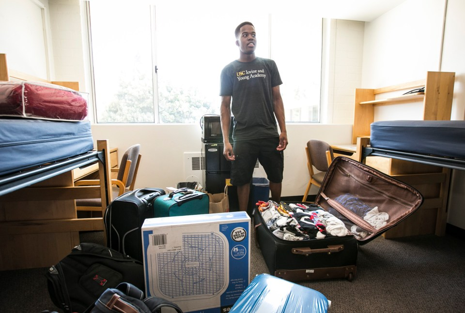 Amri Rigby standing inside his dorm unpacking his personal belongings.