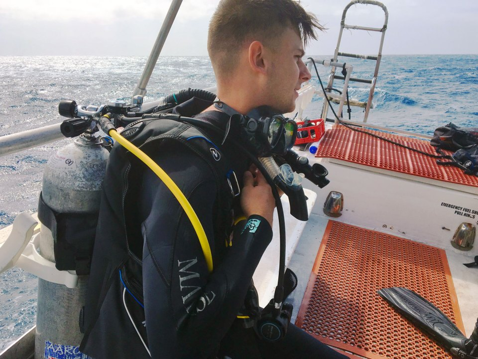 Former Marine Nicholas Foster scuba diving, sitting and prepping for a dive  from a boat at sea.