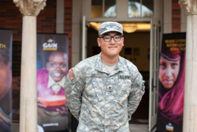 Justin Lee USC ROTC National Guardsman photographed in his uniform standing outside a building with his arms behind his back. He is smiling and looking into the camera.