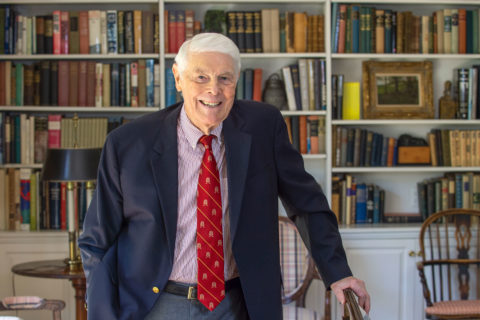 Education driven Tom Capehart oldest graduate, photographed against a shelf of books. He is wearing a business suit.