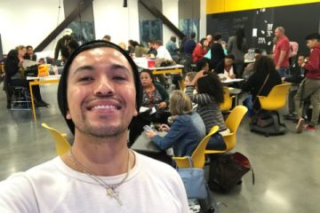 Latinx advocate Xavier Hernandez taking a selfie inside the USC Jimmy Iovine and Young academy buildng. There a mixture of students directly behind him congregating at tables.