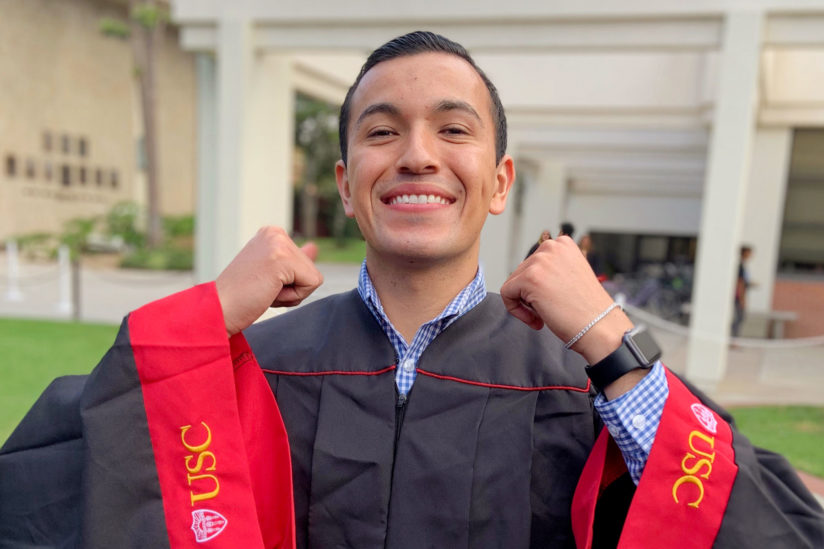 Latinx advocate Xavier Hernandez III is posing in his graduation attire.