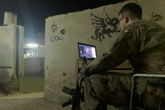Seth Holbrook enjoys the screening of his sister's film in Iraq. Seth is sitting in a chair in front of a laptop with his assault rife on the ground next to him.