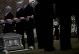 """A member of the U.S. Navy Ceremonial Guard plays """"Taps"""" during a funeral at Arlington National Cemetery on March, 8. US Navy Photo"""
