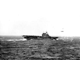 A B-25 taking off from flight deck of USS Hornet (CV-8) which is carrying a load of Army planes for raid on Tokyo as seen from USS Enterprise (CV-6). 18 April, 1942. US Naval Institute Photo