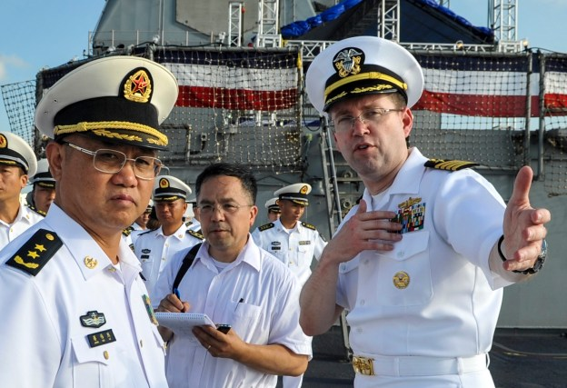Capt. James T. Jones, commanding officer of the Ticonderoga-class guided-missile cruiser USS Shiloh (CG 67), right, describes his ship to Commander of People's Liberation Army (PLA) Navy's South Sea Fleet (SSF), Vice Adm. Jiang Weilie in May. U.S. Navy Photo