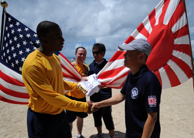 Engineering Aide 1st Class Willie Blanding presents a gift to Capt. Masahito Inoue, commanding officer of Japan Maritime Self-Defense Force (JMSDF) Sub Area Activity, Okinawa in 2013. US Navy Photo