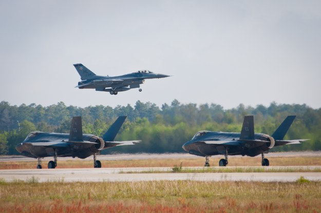 An F-16 Fighting Falcon takes off while two F-35 Lightning IIs taxi on the flightline in a training mission April 24, 2014, at Eglin Air Force Base, Fla. US Air Force Photo