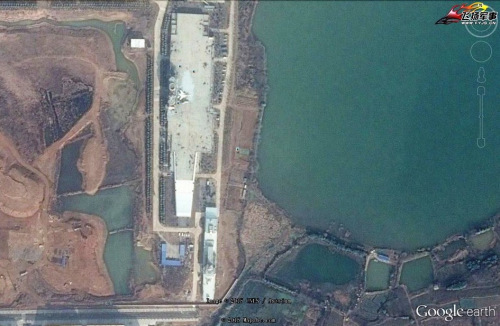 Recent Google Earth imagery of the carrier-on-land facility in Wuhan, China with the addition of a Type-55 guided missile destroyer mock-up. Google Earth Image.