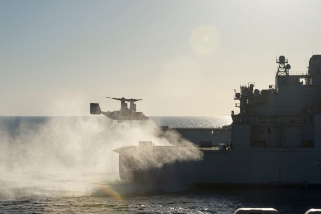 An MV-22 Osprey assigned to Marine Medium Tiltrotor Squadron (VMM) 163, Reinforced, approaches the Military Sealift Command dry cargo and ammunition ship USNS Robert E. Peary (T-AKE 5) to transport an AV-8B Harrier jet engine to the amphibious assault ship USS Makin Island (LHD 8) during a replenishment-at-sea in October 2014. US Navy photo.