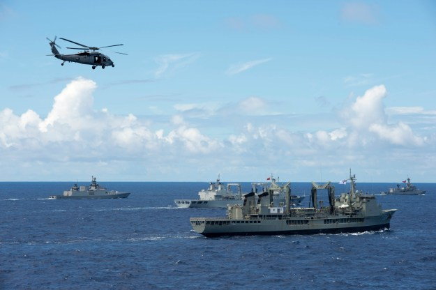 An MH-60S Sea Hawk helicopter assigned to Helicopter Sea Combat Squadron (HSC) 4 flies over several countries' ships in formation during a photo exercise for Rim of the Pacific (RIMPAC) Exercise 2014. US Navy photo.