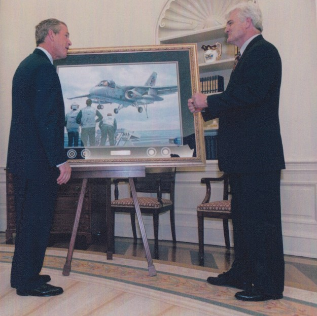 """Tom Freeman presents """"A Presidential First"""" to President George W. Bush at the White House. The painting shows the President landing in an S-3 aboard the USS Abraham Lincoln (CVN-72) on 1 May 2003. US Naval Institute Photo"""