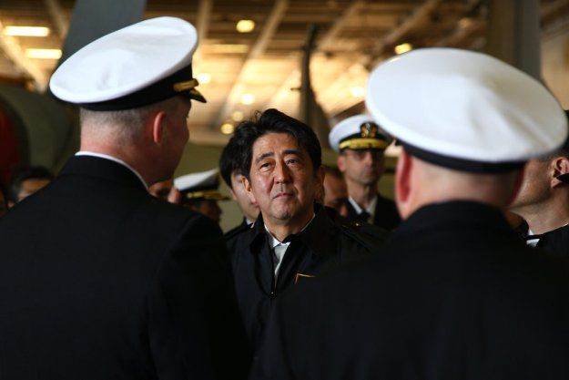 Japanese Prime Minister Shinzo Abe, center, listens as Capt. Christopher Bolt, left, commanding officer of the U.S. Navy's only forward-deployed aircraft carrier USS Ronald Reagan (CVN-76) on Oct. 18, 2015. US Navy Photo