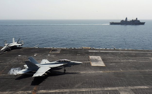 An F/A-18F Super Hornet assigned to the Bounty Hunters of Strike Fighter Squadron (VFA) 2 lands on the flight deck of the Nimitz-class aircraft carrier USS Abraham Lincoln (CVN 72) as the amphibious transport dock ship USS New Orleans (LPD 18) transits alongside in April 2012. US Navy photo.