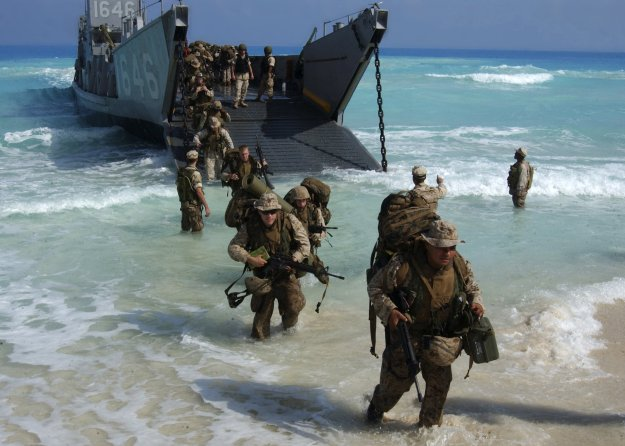 U.S. Marines from Expeditionary Strike Group One, 13th Marine Expeditionary Unit wade ashore from a landing craft. US Navy Photo