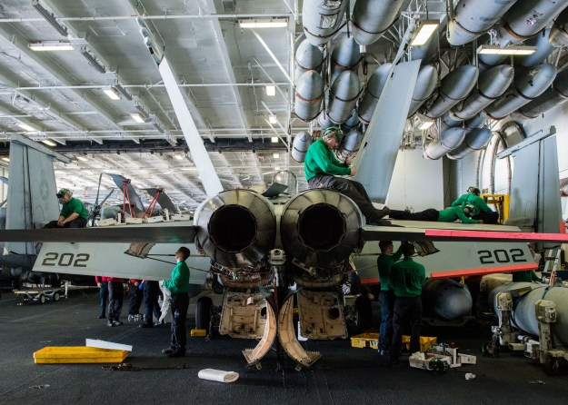 Sailors perform maintenance on an F/A-18E Super Hornet from the Top Hatters of Strike Fighter Squadron (VFA) 14 USS John C. Stennis' (CVN 74) hangar bay on Jan. 22, 2016. US Navy photo.