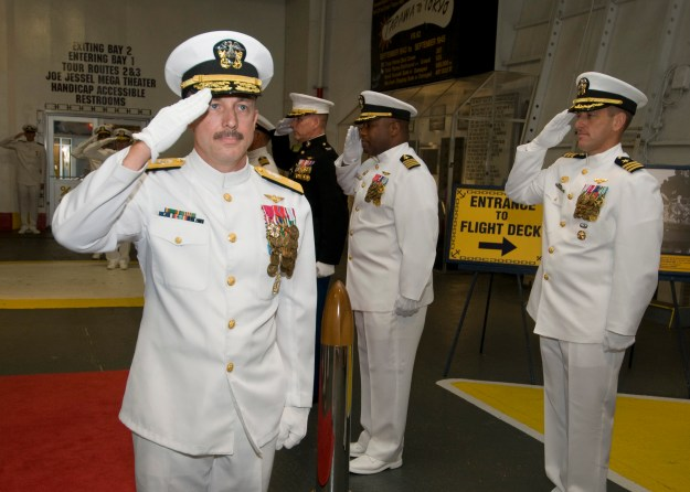 Rear Adm. Roy Kelley, incoming Chief of Naval Air Training, salutes during the arrival of the official party at a change of command ceremony at the USS Lexington Museum in September 2013. US Navy photo.
